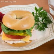 Turkey and Sharp Cheddar Bagel Sandwich with Arugula, Spinach, and Tomatoes